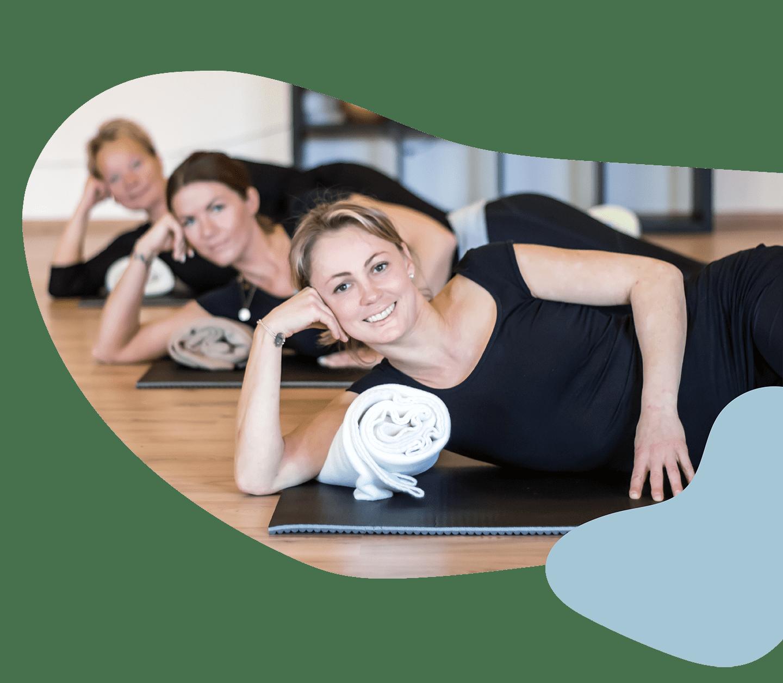 Femme Motion Villach - unsere Trainerinnen liegen im Kursraum auf den Yogamatten